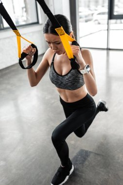 high angle view of focused young sportswoman exercising with suspension straps in gym