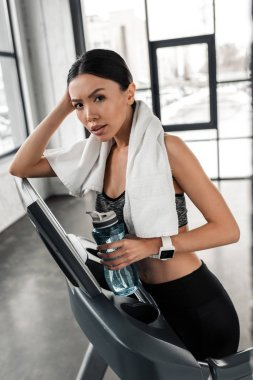 Young sportswoman with towel and bottle of water standing on treadmill and looking at camera in gym stock vector