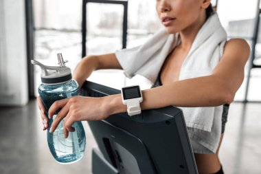 cropped shot of young sportswoman holding bottle of water and leaning at treadmill in gym
