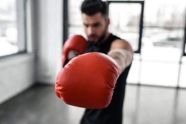 close-up view of red boxing glove and young sportsman training in gym