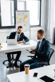 podnikatel, zatímco drží notýsek a tužku v moderní kanceláři při pohledu na spolupracovníka