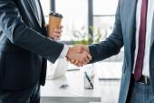 oříznutý pohled podnikatel potřesení rukou přidržujte pohárek v moderní kanceláři