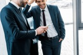 Geschäftsmann schaut auf Smartphone neben Kollege, der mit Hand in Tasche steht