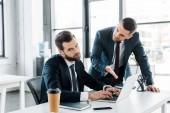 Selektivní fokus nespokojený podnikatel psaní na notebooku poblíž emocionální muže ve formálním oblečení