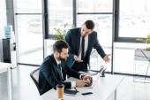 érzelmi üzletember beszélt a kolléga gépelés-ra laptop