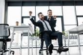 jízda na židli poblíž spolupracovníka v moderní kanceláři šťastný podnikatel