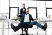 Fényképek boldog üzletember modern irodai szék, izgatott munkatárs nyomja