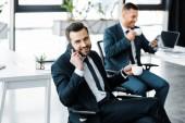 Selektivní fokus veselá podnikatel rozhovor na smartphone a zároveň drží šálek s nápojem u kolegyně