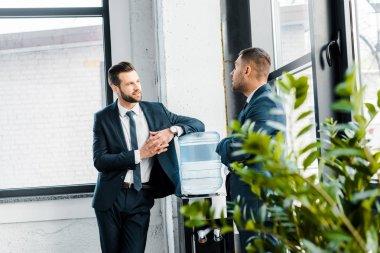 businessman in formal wear talking with coworker in modern office