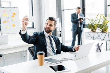 Selective focus of happy businessman taking selfie in modern office stock vector