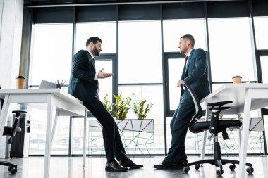 businessmen in formal wear having discussion in modern office