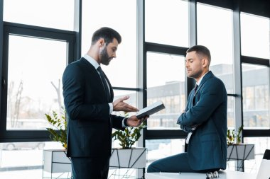 handsome businessman holding notebook and talking with colleague in modern office