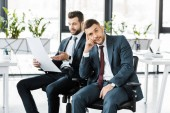selective focus of bored man in formal wear sitting near coworker with paper in hands