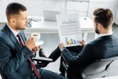 selective focus of businessman holding paper with graphs near coworker with cup of coffee