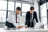 důvěru podnikatele s diskuse stoje u stolu v moderní kanceláři