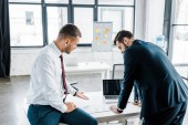 businessmen looking at document with diagram on desk in modern office