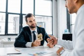 selective focus of bearded businessman holding dollar banknotes near coworker in modern office