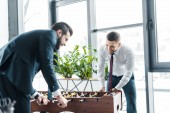 Photo smiling businessmen playing table football in modern office