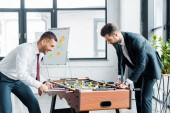 podnikatelé v oblasti formálního oblečení, hrát stolní fotbal v moderní kanceláři