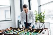 Lächelnder Geschäftsmann in festlicher Kleidung beim Tischkicker spielen