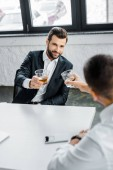 bearded businessman holding glass ow whiskey while sitting in modern office with coworker