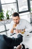 Fotografie businessman in formal wear smoking cuban cigar near coworker holding lighter in modern office