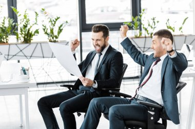 cheerful businessmen looking at paper and celebrating victory in modern office