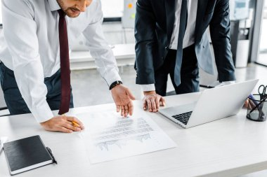 cropped view of businessmen looking at document with diagram on desk
