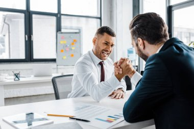 handsome businessman competing arm wrestling with coworker in modern office