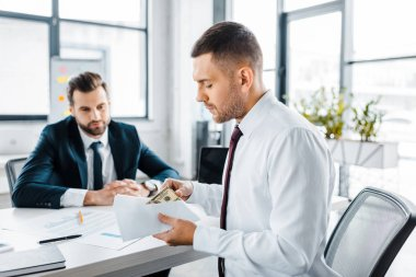 selective focus of businessman holding envelope with bribe near colleague in modern office