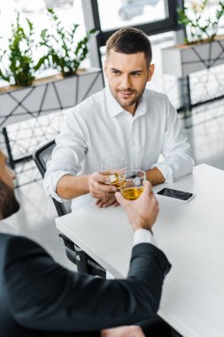 handsome businessman toasting with whiskey while sitting in modern office with coworker