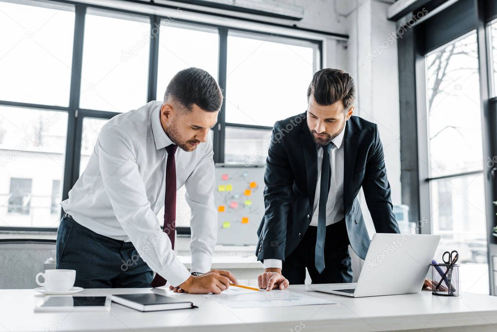 Confident businessmen having discussion while standing near desk in modern office stock vector