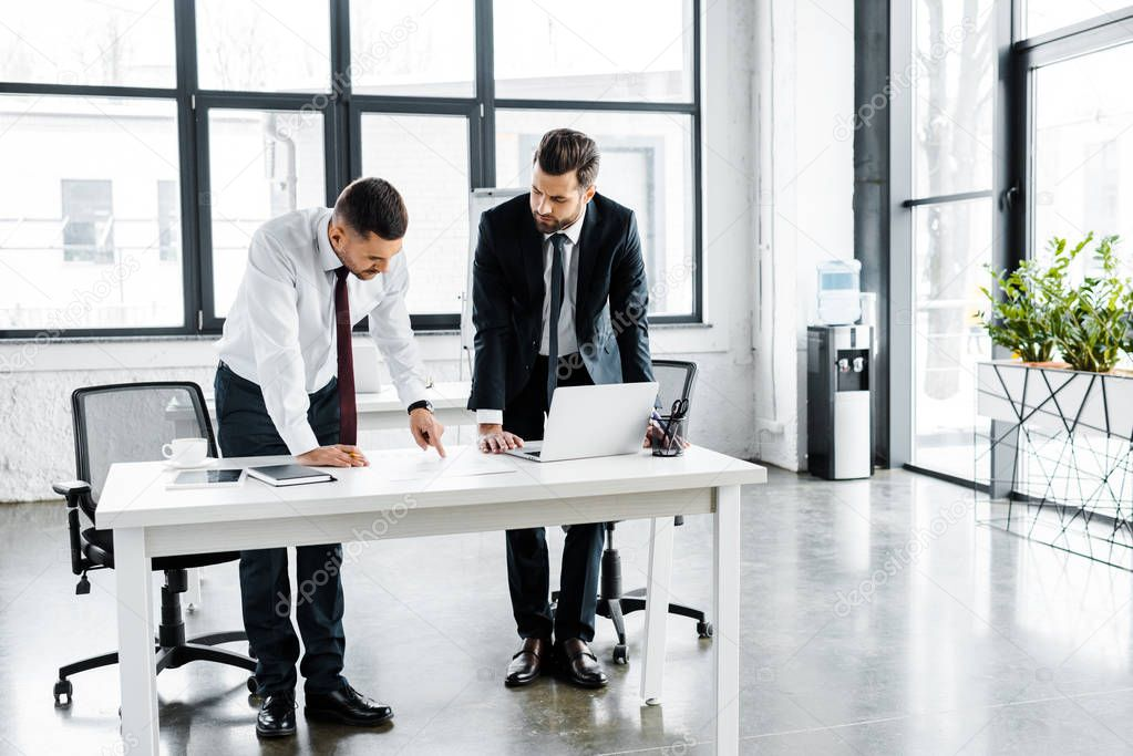 Serious businessmen having discussion while standing near desk in modern office stock vector