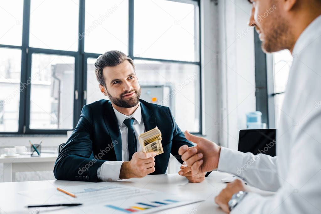 Selective focus of bearded businessman holding dollar banknotes near coworker in modern office stock vector
