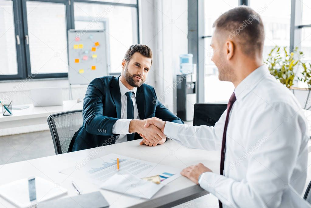 Selective focus of businessman shaking hands with coworker in modern office stock vector