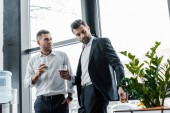 businessman standing with hand in pocket and holding glass of whiskey near coworker with cuban cigar
