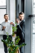 businessman pointing with finger while holding glass of whiskey near coworker with cuban cigar