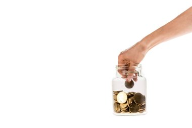cropped view of woman putting golden coin in glass jar isolated on white