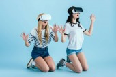 Photo Studio shot of amazed girl in VR headset standing on knees on blue background