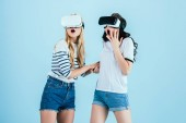 Photo Shocked girls using virtual reality headsets on blue background