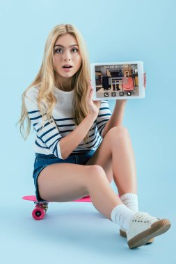Amazed blonde girl sitting on longboard and holding digital tablet with online booking app on screen on blue background stock vector
