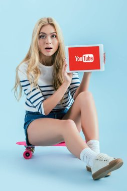 Amazed blonde woman sitting on longboard and holding digital tablet with youtube app on screen on blue background