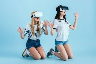 Studio shot of amazed girl in VR headset standing on knees on blue background stock vector