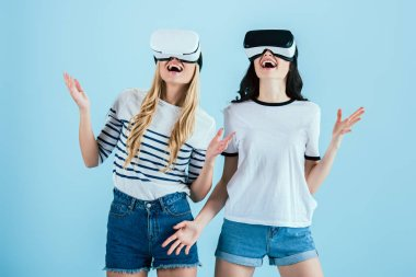 Cheerful girls using VR headsets and laughing on blue background stock vector