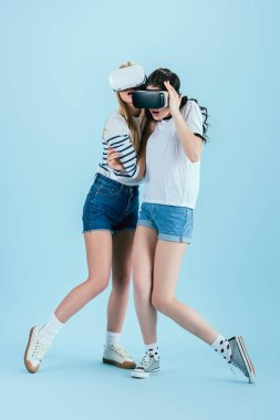 Studio shot of surprised girls in VR headsets embracing on blue background stock vector