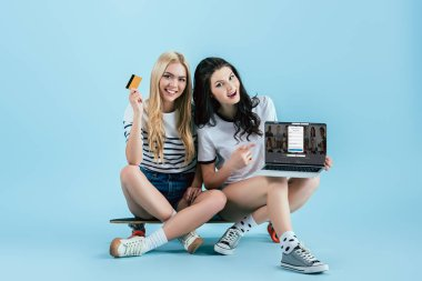 Studio shot of girls on longboard holding laptop with linkedin website on screen and credit card on blue background