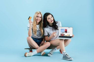 Studio shot of girls holding laptop with ebay website on screen and credit card while sitting on longboard on blue background