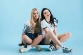 Fotografie schöne junge Frauen sitzen auf Longboard auf blauem Hintergrund