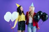 Vidám lányok party kalap tartja a léggömbök és néztek egymásra, lila háttér