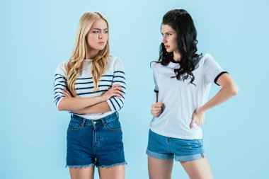 Studio shot of offended girls isolated on blue
